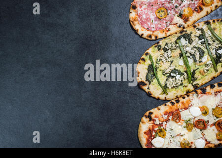 three types of pizza on dark slate with copy space - Stock Photo