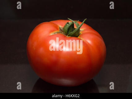 Close Up of  a Large, Ripe, Organic Tomato on a Dark Brown Counter Top, Photographed at Eye Level - Stock Photo