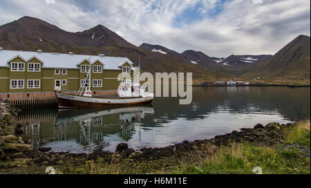 Boat next to a hotel with mountains in the background in Siglufjörður, Iceland - Stock Photo