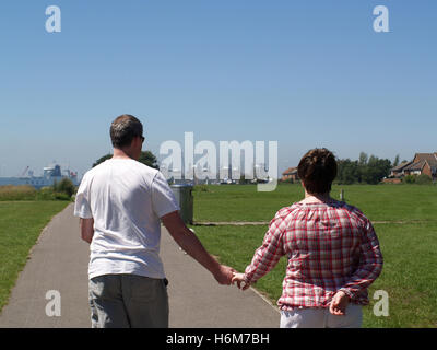 Middle aged couple walking hand in hand along Weston Shore seafront towards Woolston, Southampton, Hampshire UK - Stock Photo