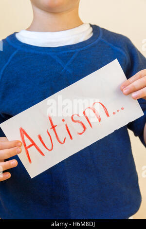 Young boy (children hands) hold Autism text written on sheet of paper close up. - Stock Photo