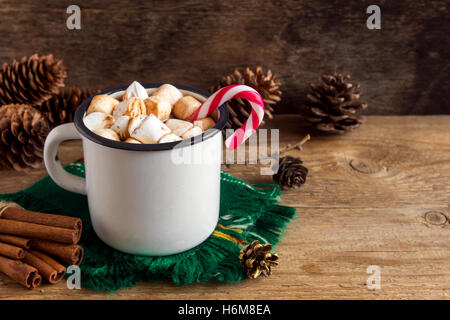 Hot chocolate with marshmallows, peppermint candy canes and cinnamon sticks in vintage metal mug - homemade hot - Stock Photo
