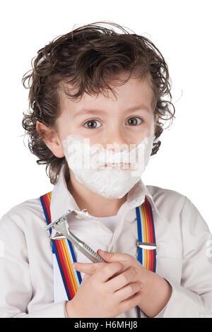Six year old boy shaving isolated on white background - Stock Photo