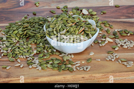 pumpkin and sunflower seeds with a few sliced almonds in a bowl and also scattered on a wooden bench - Stock Photo