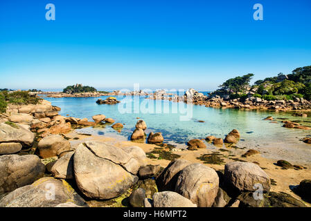 Ploumanach, rocks and bay beach in morning. Pink granite coast, Perros Guirec, Brittany, France. - Stock Photo
