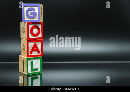 GOAL word wooden block arrange in vertical style on black background and selective focus - Stock Photo