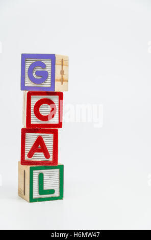 GOAL word wooden block arrange in vertical style on white background and selective focus - Stock Photo