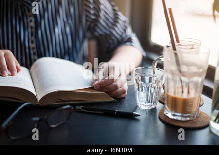 Sunday morning lifestyle scene of young hipster woman reading book in cafe with. Weekend activity or hobby concept - Stock Photo