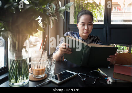 Sunday morning lifestyle scene of young hipster asian woman reading book in cafe with. Weekend activity or hobby - Stock Photo