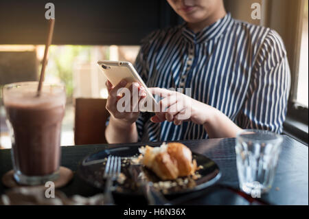 Sunday morning lifestyle scene of young hipster woman using mobile phone while sitting in cafe. Trendy lifestyle - Stock Photo