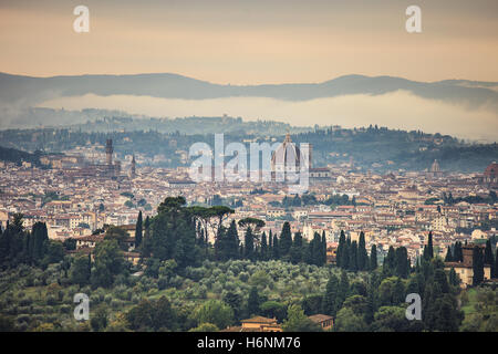 Florence or Firenze aerial foggy morning cityscape. Panorama view from Fiesole hill. Palazzo Vecchio and Duomo Cathedral. - Stock Photo