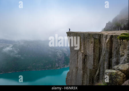 Tourist standing at Prekestolen rock's edge. - Stock Photo