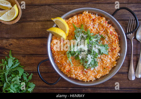 Red pepper risotto with Parmesan and rocket - Stock Photo