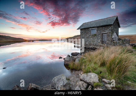 Sunset over an old stone boathouse on the shores of Devoke Water, a remote lake on Birker Fell in the Lake District - Stock Photo