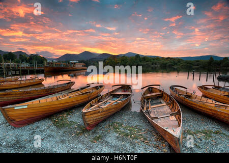 Stunning sunset over wooden rowing boats on Derwentwater at Keswick in the Lake District Nationla Park in Cumbria - Stock Photo