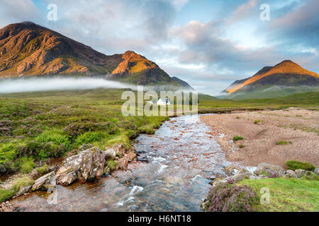 The rising sun lighting the mountain peaks at Glencoe in the Highlands of Scotland - Stock Photo