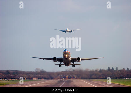 N773AN American Airlines Boeing 777-223/ER takes off while A6-EBW Emirates Boeing 777-31H/ER lands at London Gatwick. - Stock Photo