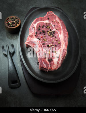 vertical dark and moody image of a raw succulent steak with a small pot of pepper corns in the background. room - Stock Photo
