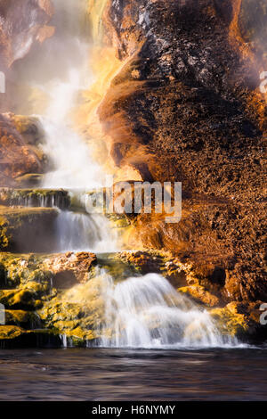 A small waterfall from a hotspring in Yellowstone National Park flows down a rock formation - stained many colors - Stock Photo
