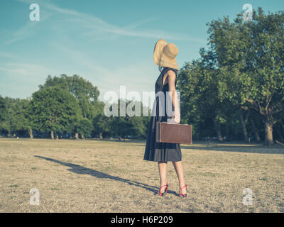 Vintage filtered shot of an elegant young woman wearing a dress and a hat standing in the park with a briefcase - Stock Photo