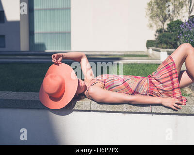 A young woman wearing a dress and a hat is relaxing outside on a sunny summer day - Stock Photo