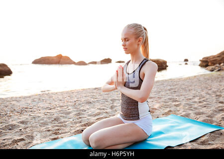 Portrait of relaxed young woman meditating outdoors on beach - Stock Photo