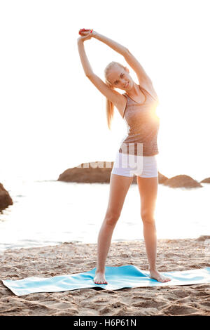 Happy smiling woman doing stretching exercises during yoga on the beach - Stock Photo