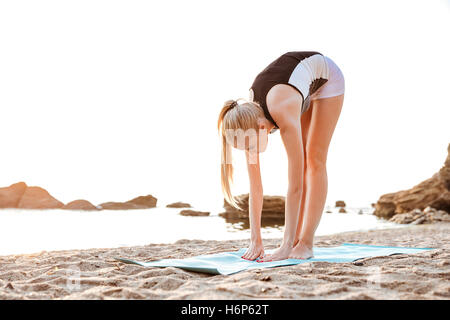 Young woman doing yoga exercises on mat outdoors in the morning - Stock Photo