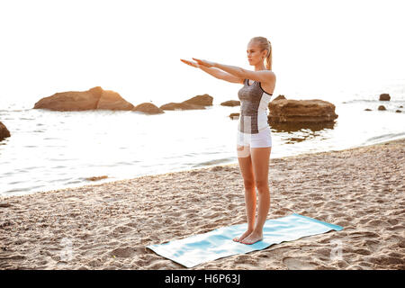 Beautiful young woman doing stretching exercises during yoga on the beach - Stock Photo