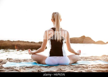 Back view of a young woman sitting in lotus position on beach - Stock Photo