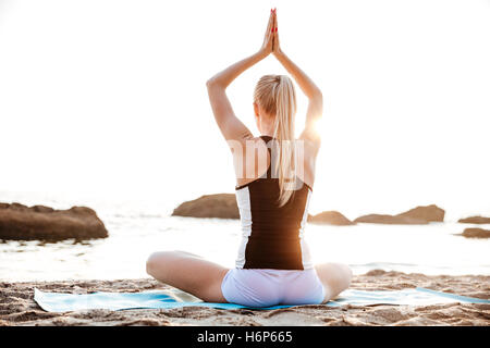 Back view of a young woman sitting and meditating on beach - Stock Photo
