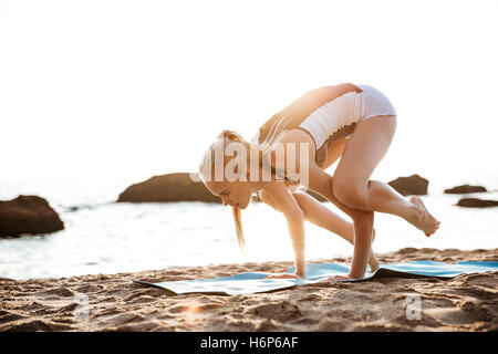 Beautiful young woman balancing on hands and practicing yoga on mat outdoors - Stock Photo