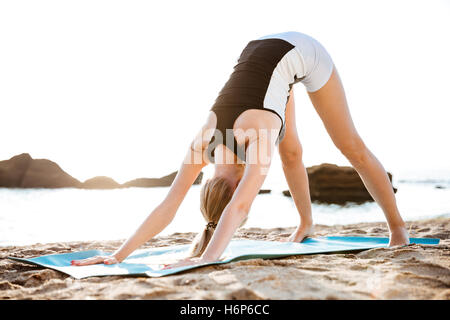 Young woman doing yoga exercises on yoga mat on beach in the morning - Stock Photo