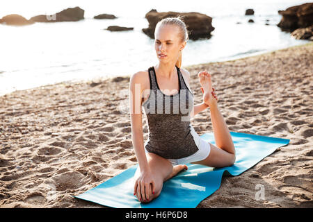 Happy fitness woman doing stretching exercises on the beach - Stock Photo