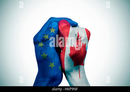 a hand patterned with the flag of the European Community envelops another hand patterned with the flag of Canada - Stock Photo