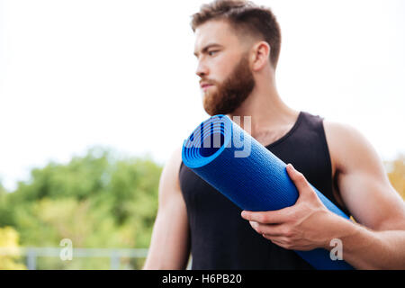 Serious male yoga instructor holding mat and looking away standing outdoors - Stock Photo