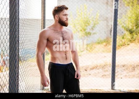 Handsome young shirtless fitness man resting during workout outdoors - Stock Photo