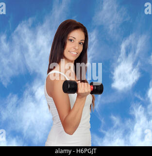 Attractive brunette girl tightening their muscles with a beautiful sky of background - Stock Photo