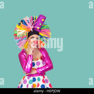 Pensive girl clown with a big colorful wig on green background - Stock Photo