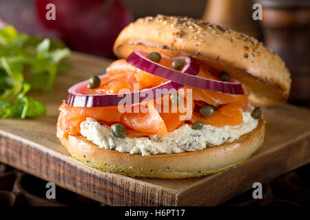 A delicious toasted bagel with smoked salmon, cream cheese, capers, and red onion. - Stock Photo
