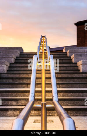 Shiny metal handrail illuminated from beneath at sunset on the steps at Granary Square, King's Cross, London, UK - Stock Photo
