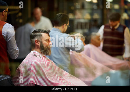 Gents barber hairdresser grooming male   busy street  Shops shopping shopper store retail retailer retail retailers - Stock Photo