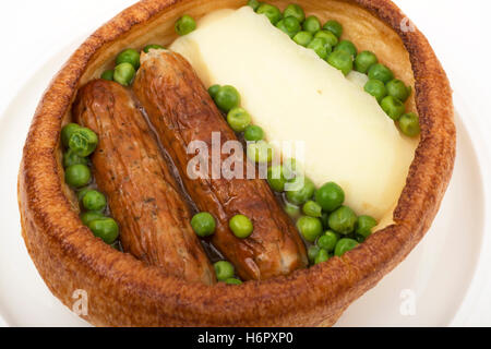 'Toad in the hole' Yorkshire pudding, sausage, mashed potatoes and peas - Stock Photo