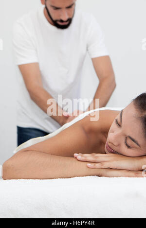 masseur giving massage treatment at spa - Stock Photo