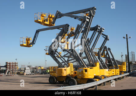 A row of 9 mobile elevating work platforms in a yard with their booms elevated in a range of positions - Stock Photo