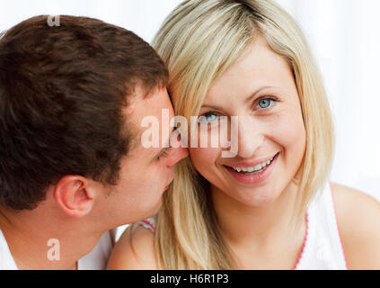Close-up of a man whispering a woman something funny - Stock Photo