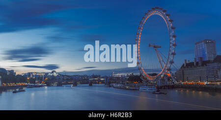The iconic London Eye ferris wheel on a blue summer's evening lighting up the river and overseeing the boats. - Stock Photo