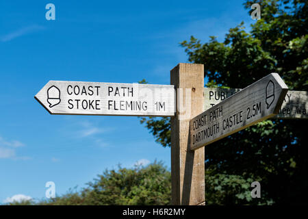 Countryside wooden finger post pointing Coast Path, Stoke Fleming and Dartmouth Castle against trees and a clear - Stock Photo