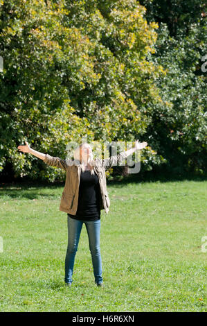 young woman spreads her arms out - Stock Photo