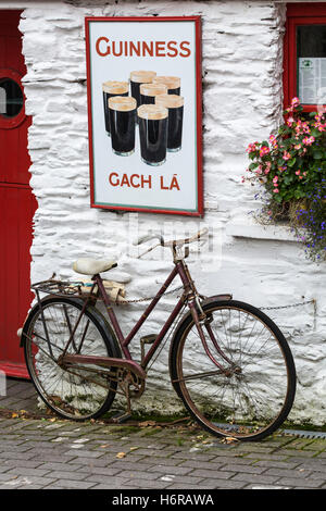 Old bicycle and Guinnes advertising outside An Teach Beag, the little house, pub in Union Hall, glandore, County - Stock Photo